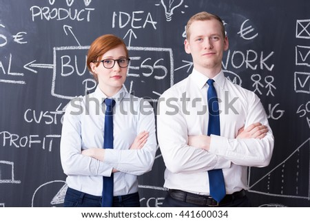 Ambitious young man and woman standing next to each other, business plan drawn on a blackboard in the background