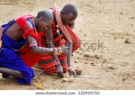 AMBOSELI, KENYA-OCT. 13: Portrait of unidentified young Maasai warriors shows how to make fire in a traditional way to guests visiting their village taken on Oct 13, 2011 in Masai Mara, Kenya.