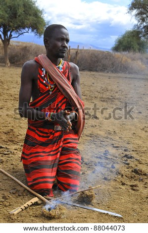 AMBOSELI, KENYA ,OCT. 13: Portrait of young Maasai  warrior showing how they make fire in a traditional way to guests visiting their village taken on Oct 13, 2011 in Masai Mara, Kenya. - stock photo