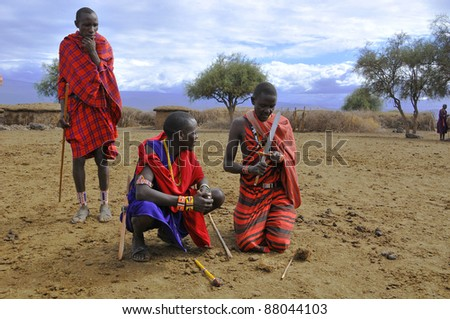 AMBOSELI, KENYA ,OCT. 13: Portrait of young Maasai  warriors showing how they make fire in a traditional way to guests visiting their village taken on Oct 13, 2011 in Masai Mara, Kenya. - stock photo