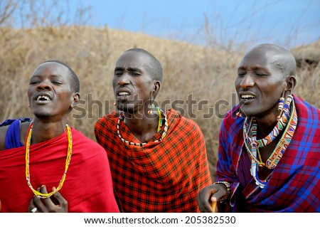 AMBOSELI, KENYA - OCT 13: Unidentified African people from Masai tribe prepare to show a traditional Jump dance on Oct 13, 2011 in Masai Mara, Kenya. They are nomadic and live in small villages. - stock photo