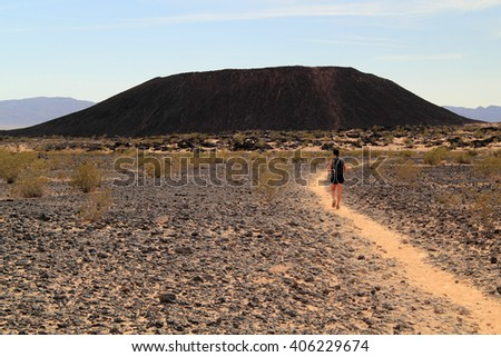 AMBOY, CA - MARCH 27, 2016: A female hiker approaches Amboy Crater, an extinct volcano in southern California March 27, 2016 in Amboy, California. - stock photo