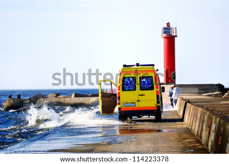 Ambulance car rescuing people at the sea shore during storm stock