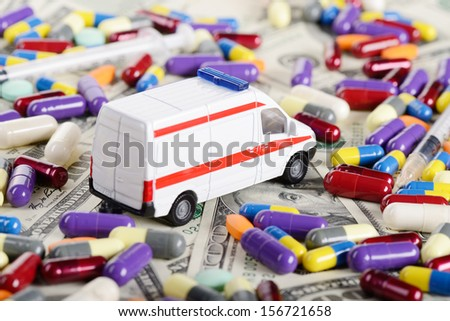 Ambulance car toy ride through dollars, pills and syringes (Installation on the theme of modern medicine) - stock photo