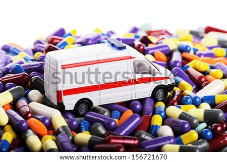 Ambulance car toy ride through pills (Installation on the theme of modern medicine) - stock photo