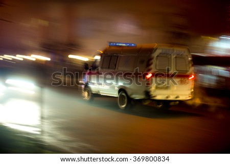 Ambulance in motion driving down the road at night. Intentional motion blur - stock photo