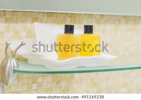 Amenities kit on shelf cream, shampoo and shower in the bathroom