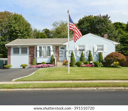 America Flag pole Beautiful Landscaped Suburban Ranch Style Home Residential Neighborhood USA - stock photo