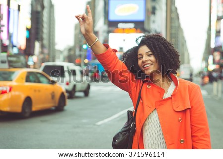 America woman calling a taxi in Manhattan. Good mood and hand up to stop the yellow cab - stock photo