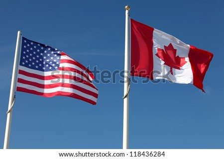 American and Canadian flags waving against a blue sky - stock photo