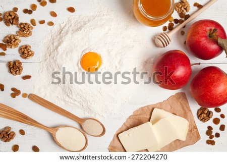 American apple pie preparation in rustic kitchen. Raw ingredients on white table such as yeast, butter, apples, flour, eggs, raisins and honey - stock photo