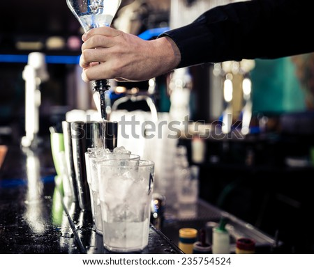 american bartending calling order. bartender pouring in one tin - stock photo