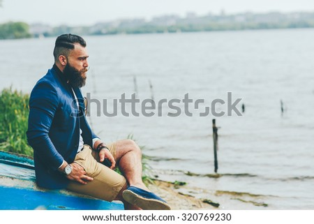 American Bearded Man looks on the river bank in a blue jacket