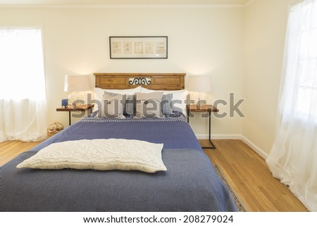 American bedroom with blue bed sheets with night stands and natural fibers rug - stock photo