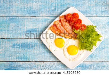 American Breakfast Eggs and bacon with tomato and lettuce on a wooden background - stock photo