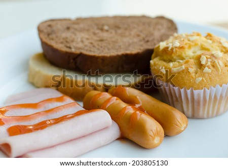 American breakfast with ham, sausage, bread and cup cake. - stock photo
