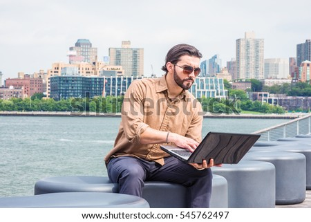 American Business Man traveling, working in New York, wearing brown shirt, sunglasses, sitting on bench at park by East River, reading laptop computer. Brooklyn on background. Color filtered effect.