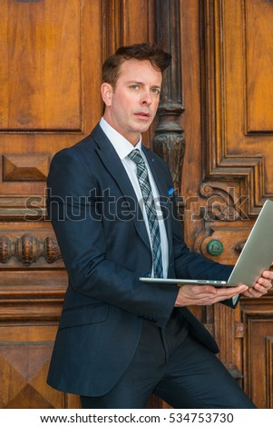 American Business Man working in New York., wearing black suit, patterned necktie, white shirt, standing by vintage office doorway, reading, working on laptop computer, thinking.