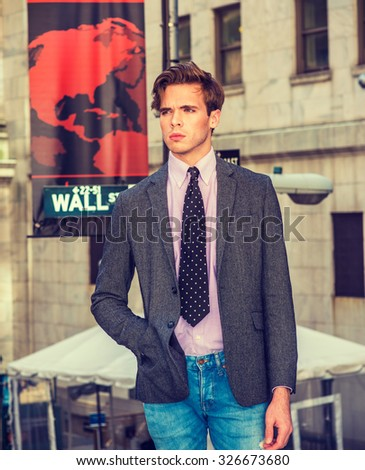 American businessman in New York. Young college student, wearing gray patterned blazer, light pink undershirt, black, white polkadot necktie, standing on street, thinking. Instagram filtered effect. - stock photo