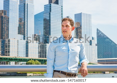 American businessman traveling in New York in hot summer, wearing white shirt, standing by metal fence in busy business district with high buildings under sun, looking away.
