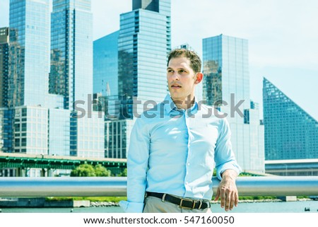 American businessman traveling in New York in hot summer, wearing white shirt, standing by metal fence in busy business district with high buildings under sun, looking away. Color filtered effect