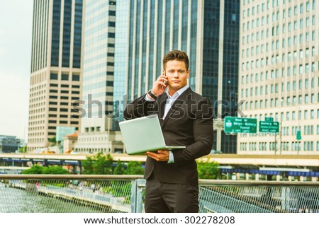 American businessman traveling, working in New York. Dressing in black suit, a young sexy man working on laptop computer, calling on phone in business district, confident, successful. Instagram effect