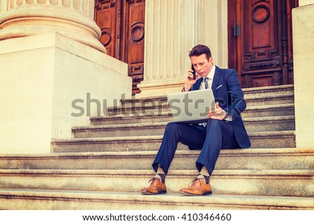 American Businessman traveling, working in New York, dressing in black suit, leather shoes, sitting on stairs outside office, working on laptop computer, calling on phone. Instagram filtered effect.  - stock photo