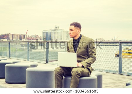American Businessman traveling, working in New York, wearing green suit, black undershirt, sitting on street park by river, working on laptop computer, looking around, thinking. Brooklyn on background