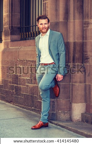 American Businessman with beard, mustache traveling in New York, wearing cadet blue suit, white undershirt, brown leather shoes, standing against vintage wall with window on street. Instagram effect.  - stock photo