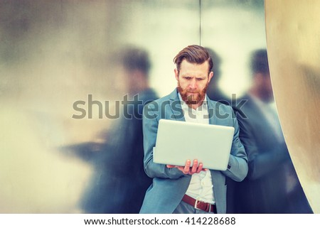 American Businessman with beard, mustache working in New York, wearing cadet blue suit, standing against silver metal wall, looking down, working on laptop computer.   - stock photo