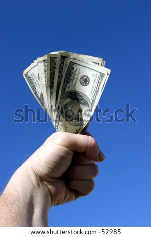 american cash being held tight in the fist of a real humanbeing against a blue sky background - stock photo