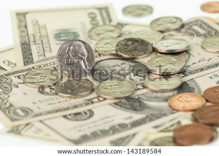 American coins scattered on top of US one dollar bills and one hundred dollar bills close up - stock photo