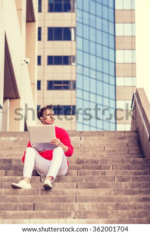 American college student reading, working on laptop computer, wearing red knit sweater, white pants, shoes, sitting on stairs outside in New York, looking away, thinking. Instagram filtered effect. - stock photo