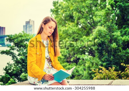 American college student studying in New York. A pretty girl wearing flower patterned underdress, yellow corduroy jacket, holding green book, sitting by trees on campus, looking down, reading. - stock photo
