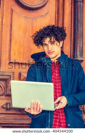 American college student studying in New York. Wearing blue jacket with hood, a guy with freckle face, curly long hair, standing by vintage classroom doorway, reading, working on laptop computer.  - stock photo