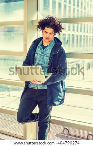 American college student studying in New York. Wearing blue jacket with hood, a guy with freckle face, curly long hair, standing against glass wall on campus, reading, working on laptop computer.  - stock photo