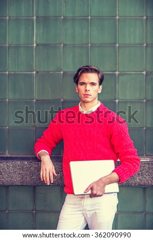 American college student studying in New York, wearing red knit sweater, white pants, holding laptop computer, standing against green wall on campus, looking forward, Instagram filtered effect.  - stock photo