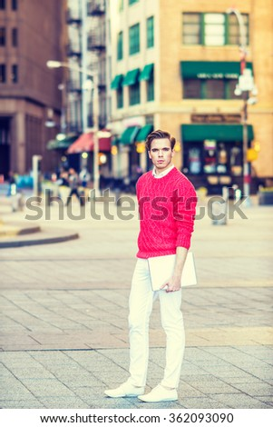 American college student studying in New York, wearing red knit sweater, white pants, shoes, holding laptop computer, standing on street, confidently looking forward, Instagram filtered effect. - stock photo