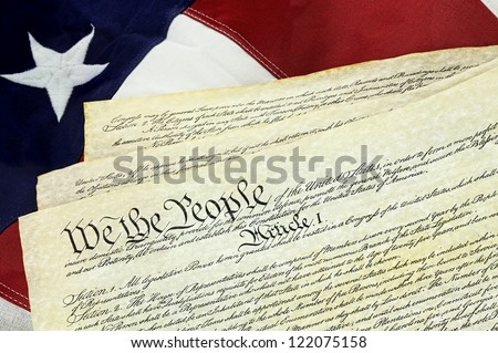 American Constitution lying over top of the US flag. - stock photo