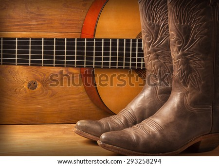 American Country music with guitar and cowboy shoes on wood - stock photo
