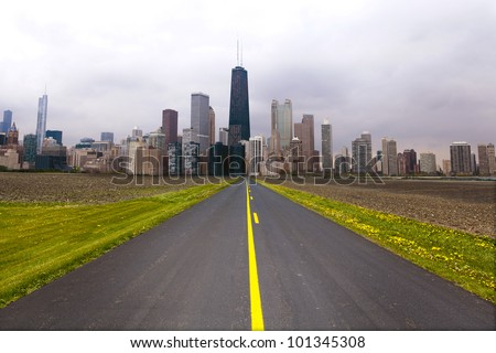 American Country Road with City on the Horizon - stock photo