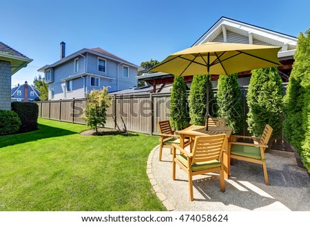 American craftsman house exterior. Small Patio area with wooden table set and umbrella. Green thuja trees in pots and well kept lawn. Northwest, USA