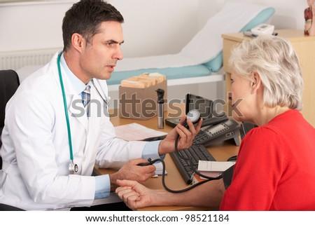 American doctor taking senior woman's blood pressure - stock photo