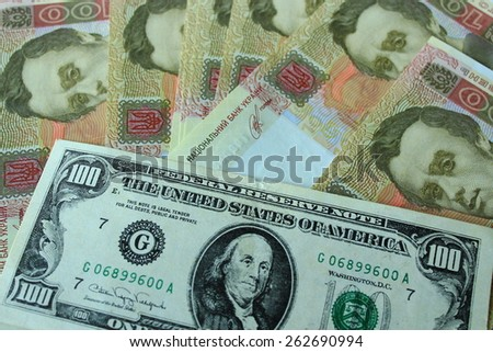 American dollar and grivnas banknotes isolated on dark background - stock photo