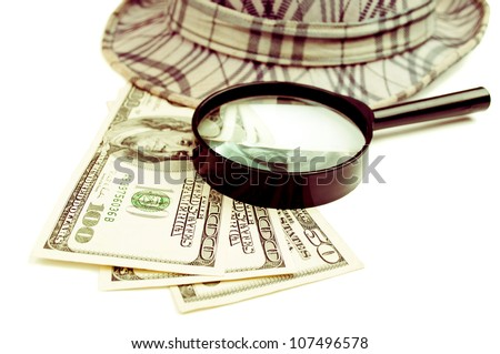 American Dollar-bills, magnifying glass and hat, isolated on white - stock photo