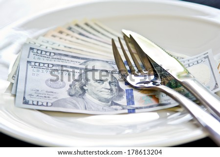 American Dollar note on white plate by cutlery
