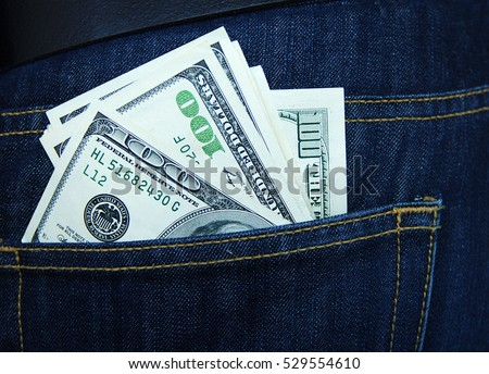 American dollars, hundred-dollar notes, sticking out of the blue jeans pocket. Pocket in blue jeans with hundred and more US dollar. Business concept exchange