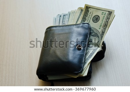 American dollars in a black leather wallets - stock photo