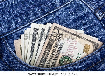 American dollars sticking out of the blue jeans pocket