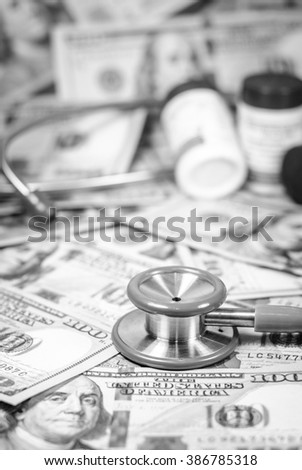 American dollars with stethoscope costs for the medical insurance on black and white color,Focus on stethoscope and blurry background - stock photo